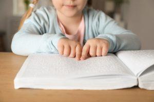 Foto de criança lendo em braile