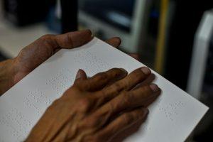 Foto em close de duas mãos deslizando sobre uma folha de papel com texto em braile.