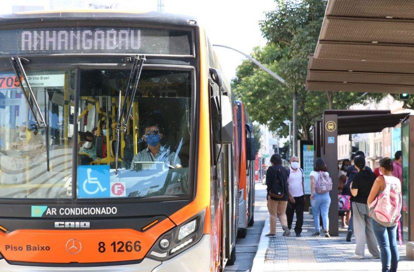 Foto de um ônibus parado em um ponto cheio de pessoas.