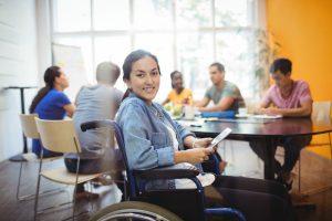 Foto de uma mulher, cadeirante, sorrindo para a câmera. Ela está em uma sala de reunião e ao fundo, envolta de uma mesa, há um grupo de pessoas.