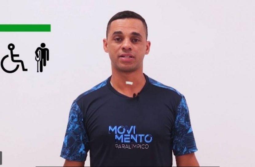 """Print de um vídeo com Everaldo Lúcio, treinador da Seleção Brasileira paralímpica de atletismo. Ele usa uma camiseta azul com o logo do """"Movimento Paralímpico"""". Ao lado esquerdo, há símbolos de acessibilidade."""