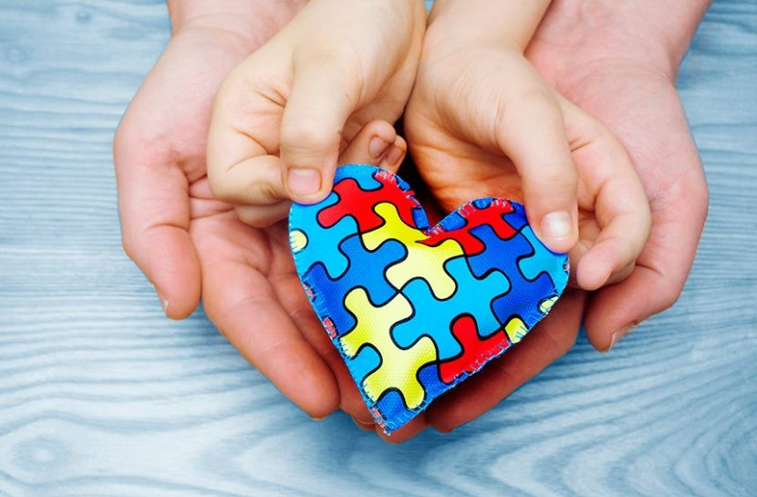 Foto, em close, de um par de mãos adultas abertas em concha. Elas apoiam um par de mãos infantis, que, por sua vez, seguram juntas um coração de feltro estampado com um quebra cabeça colorido.