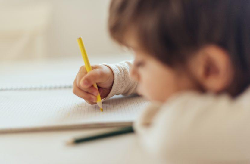Foto de uma criança com um lápis amarelo na mão direita, sobre um caderno aberto. Ela está com o rosto apoiado sobre o caderno.