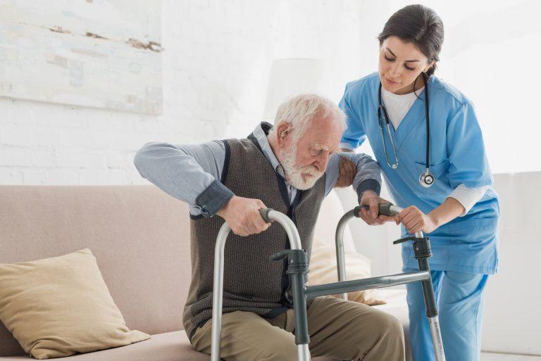 Foto de um homem idoso levantando de um sofá apoiado em um andador e com a ajuda de uma enfermeira.