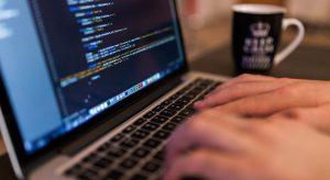 Foto em close de duas mãos digitando no teclado de um notebook. Na tela do equipamento, há uma tela preta com linhas de códigos.