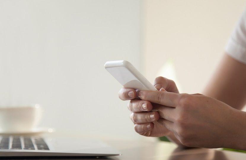 Foto de mãos femininas segurando um celular.
