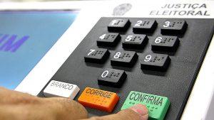 Foto em close do teclado numérico de uma urna eletrônica e a mão de uma pessoa apertando a tecla verde de confirmação.