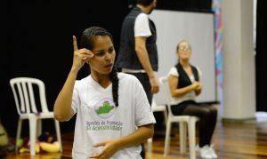 Foto de uma jovem fazendo um sinal em Libras. Ela veste uma camiseta branca com a frase Agentes de Promoção da Acessibilidade.