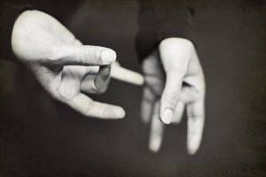Foto em branco e preto, fundo escuro, com mãos fazendo o sinal de especial na língua de sinais