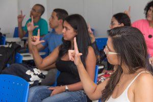 Foto de uma sala de aula com alunos sentados em carteiras escolares azuis, fazendo o sinal da letra L em Libras