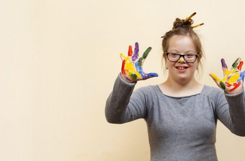 Foto de uma jovem com Síndrome de Down com os braços levantados. As palmas das mãos estão abertas e sujas com tinta. Ela sorri.