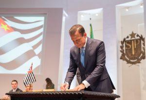Foto de João Doria, governador de SP, assinando um documento sobre uma mesa de madeira.