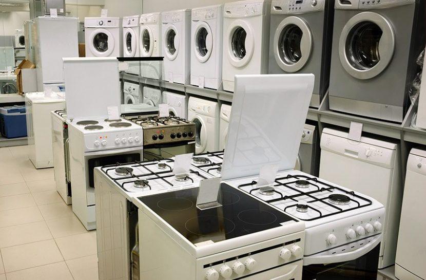 Foto de modelos de fogões e máquinas de lavar roupa expostos em uma loja.