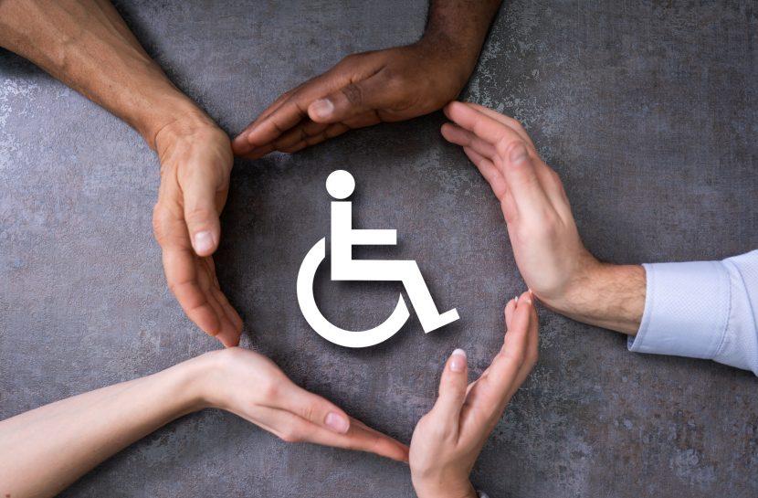 Imagem de um ícone de cadeirante pintado sobre uma superfície cinza, e cinco mãos direitas, de diferentes tons de pele, fechando um círculo ao redor do ícone