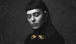 Foto em branco e preto da Sophie Harrocks de olhos fechados, com detalhes dourados do Sensaura na sua orelha esquerda e pescoço.