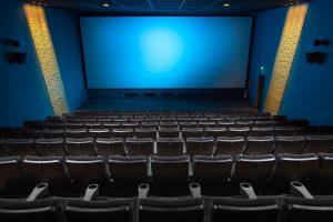Imagem de uma sala de cinema vazia, com poltronas pretas em formato de arquibancada.