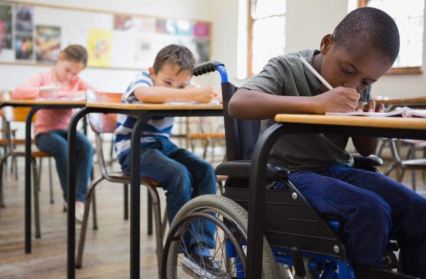 Foto de um grupo de crianças sentadas em uma sala de aula, sendo que uma delas é cadeirante