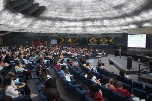 Foto de um grupo diverso de pessoas no auditório do Memorial da Inclusão.