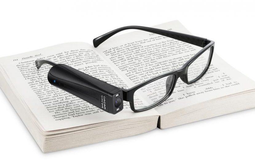 Foto de um óculos, em cima de um livro aberto, com o dispositivo OrCam MyEyes acoplado em uma de suas hastes