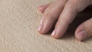 Foto em close dedos sobre papel em relevo de escrita tátil, braille.
