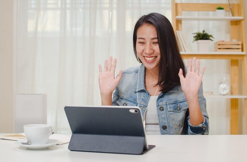 Foto de uma mulher sentada em frente a um tablet. Ela está com fones de ouvido e com as mãos levantadas.