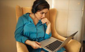 Foto de uma mulher, sentada em uma poltrona, com um laptop em cima das pernas. Ela usa um fone de ouvido e olha para a tela do computador.