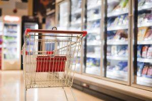 Foto de um carrinho de supermercado parado em frente a uma geladeira com produtos refrigerados