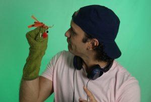 Foto de um homem com um fantoche na mão direita. Ele está de lado e olha para o boneco.