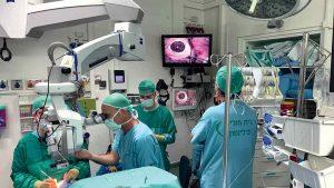 Foto de quatro pessoas em uma sala de cirurgia durante o transplante de córnea
