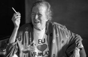 Foto em preto e branco de Hilda Hilst. Ela está com um cigarro em uma das mãos, os olhos fechados e sorrindo.