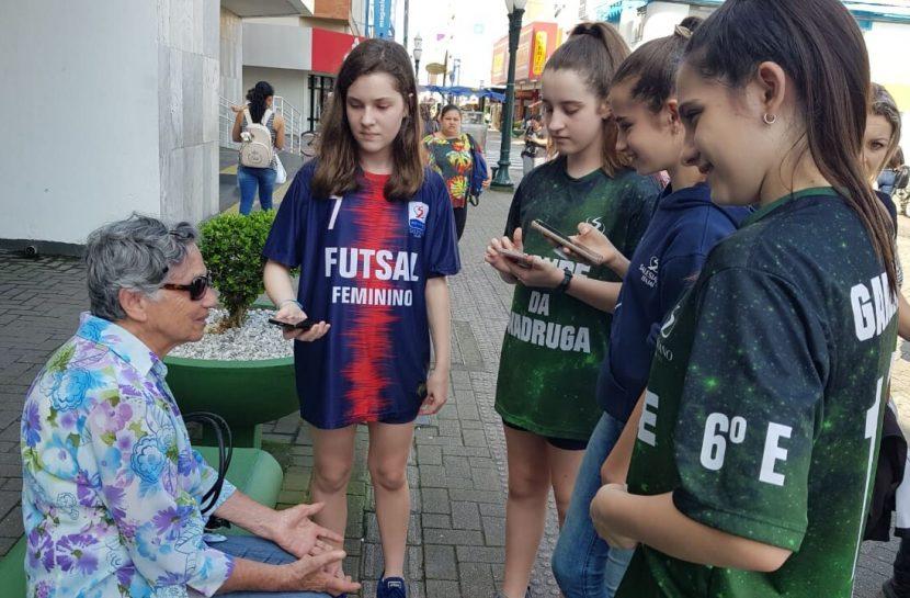 Foto de um grupo de meninas conversando com uma idosa sentada no banco de uma praça