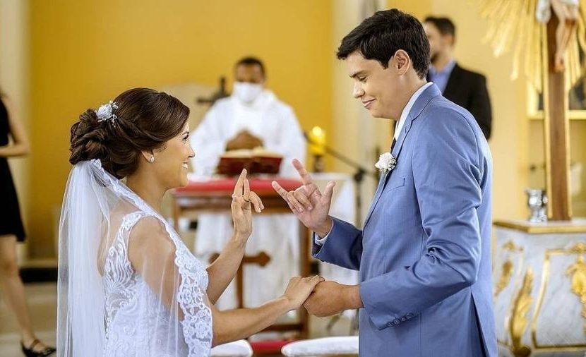 Foto de Adrielly e Adalberto um de frente para o outro fazendo sinal de eu te amo com uma das mãos