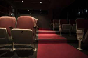 Foto de uma sala de cinema com poltronas vazias