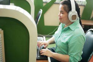 Foto de uma jovem com deficiência visual sando fones de ouvindo e digitando no teclado de um computador.