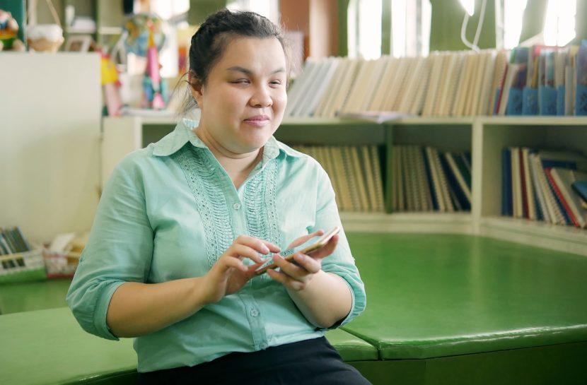 Foto de uma mulher cega sentada. Em sua mão está um smartphone.