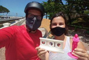 Foto em estilo selfie de Renato Frosch ao lado de uma mulher. Ela segura dois monumentos impressos em 3D