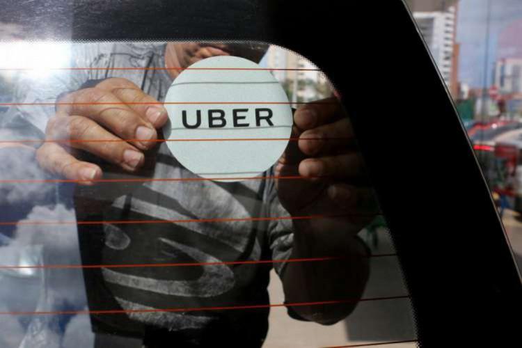 Foto de um homem colando um adesivo da Uber no vidro de um carro