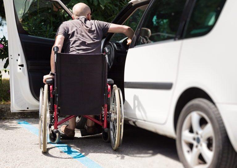 Foto de um homem cadeirante ao lado de um carro com a porta aberta.