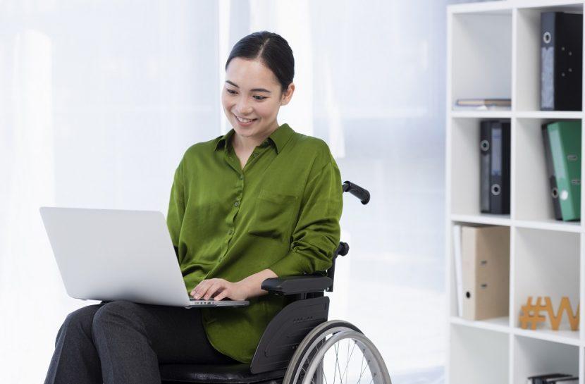 Foto de uma mulher cadeirante em uma sala. Ela está com um laptop no colo.