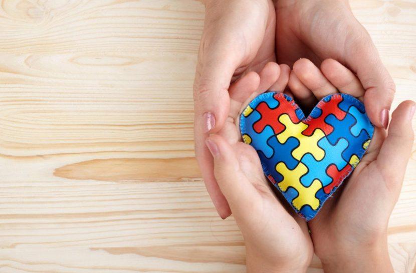 Foto com dois pares de mãos unidos segurando um coração de feltro com estampa de quebra-cabeça nas cores do autismo