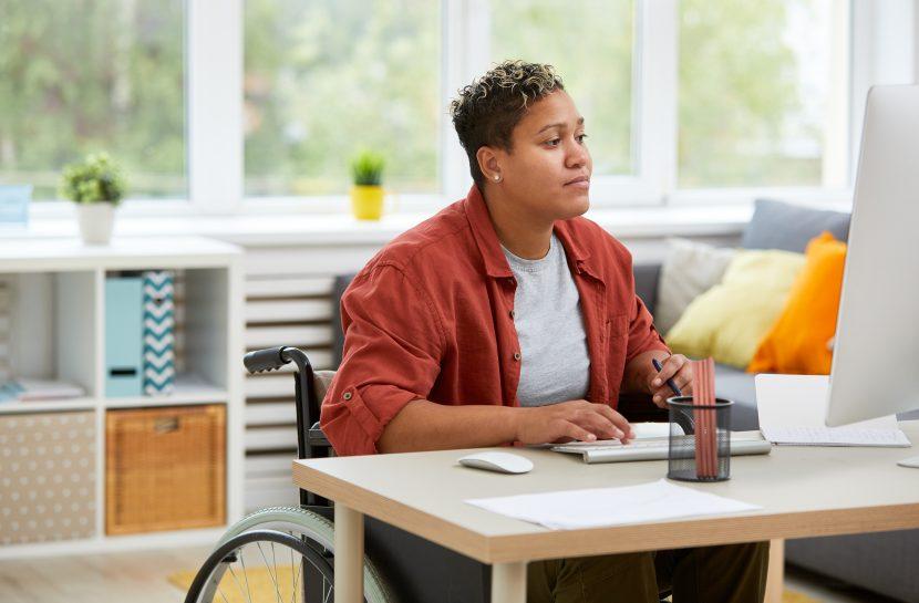 Foto de uma mulher cadeirante em uma sala. Ela está digitando no teclado de um computador.