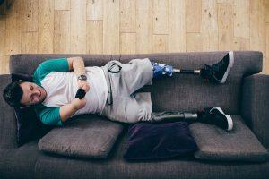 Foto vista de cima de um rapaz deitado num sofá, sorrindo, mexendo no celular