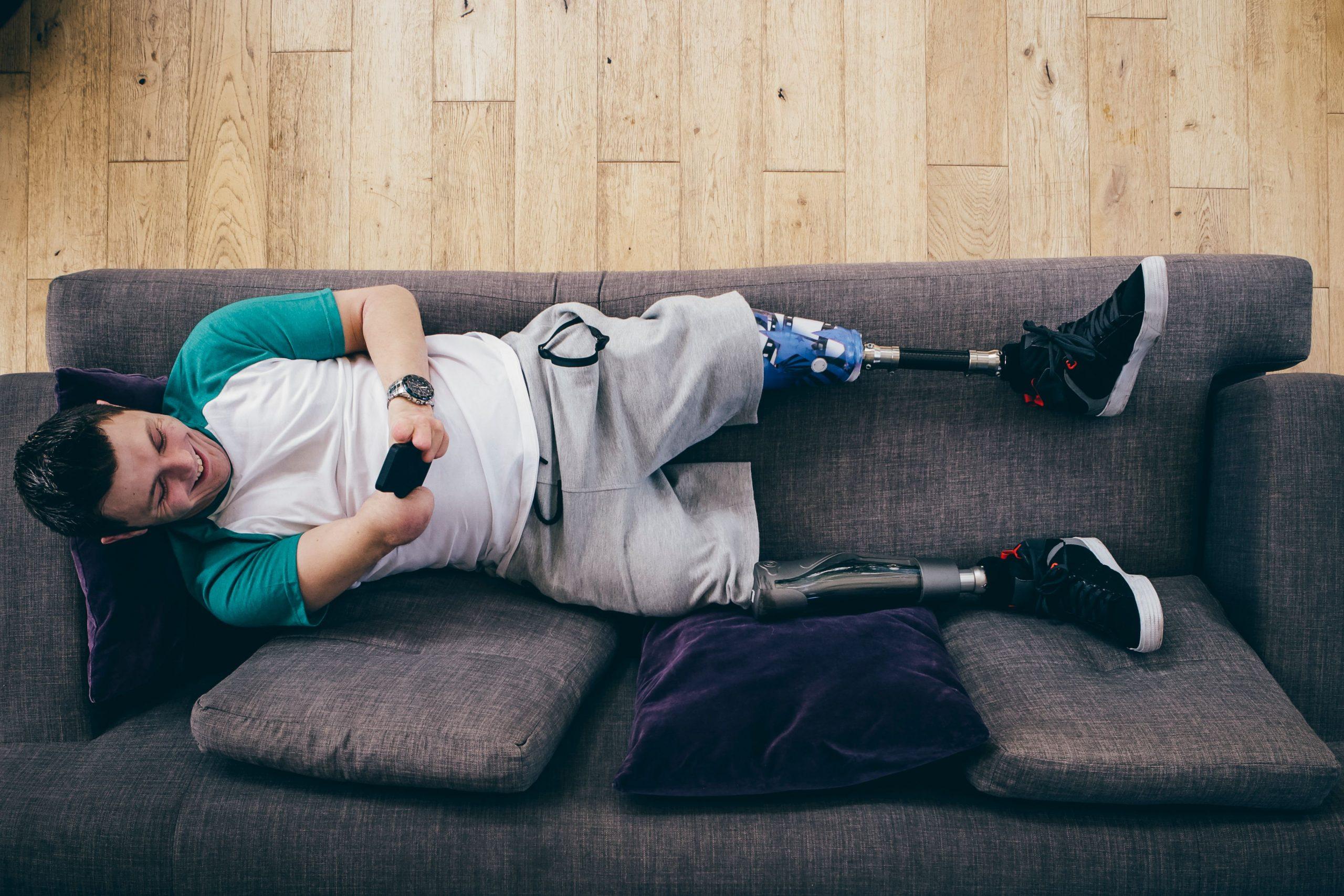 Foto de um rapaz deitado num sofá, sorrindo, mexendo no celular. Ele tem cabelos curtos e castanhos, está de camiseta branca e azul, e bermudas de moletom cinza. Ele usa próteses trans-femurais nas pernas direita e esquerda. O braço direito é amputado abaixo do cotovelo, assim como os dedos da mão esquerda, a partir das falanges médias.
