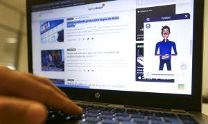Foto da tela de um notebook no site da Agência Brasil, com o avatar da VLibras à direita, no canto da tela. Sobre o teclado do computador, há a mão de uma pessoa, como se estivesse digitando.