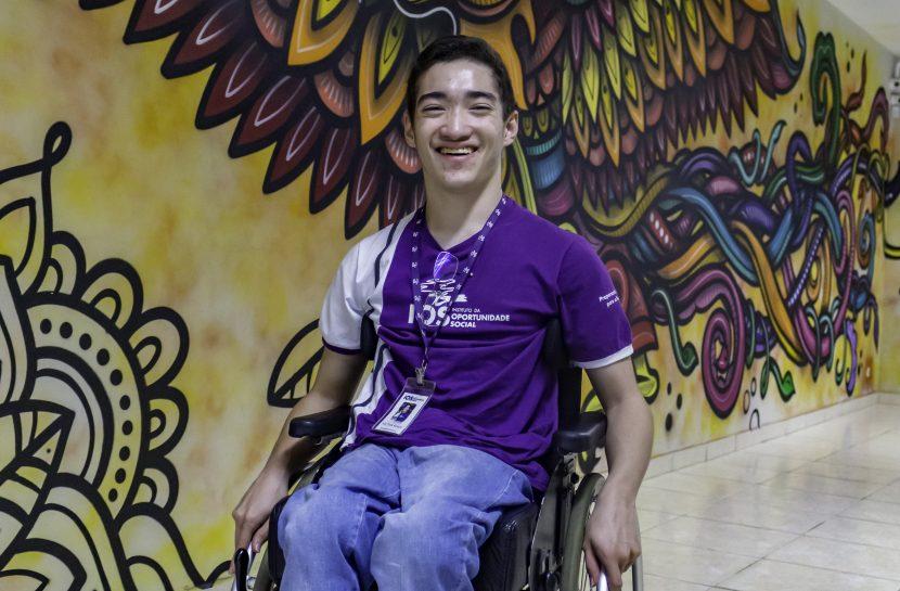 Foto de um aluno cadeirante da IOS. Ele está sorrindo para a câmera, com um crachá no pescoço, vestindo uma camiseta roxa do Instituto da Oportunidade Social, calças jeans e tênis. Atrás dele, uma parede longa grafitada em diversas cores, com artes variadas.