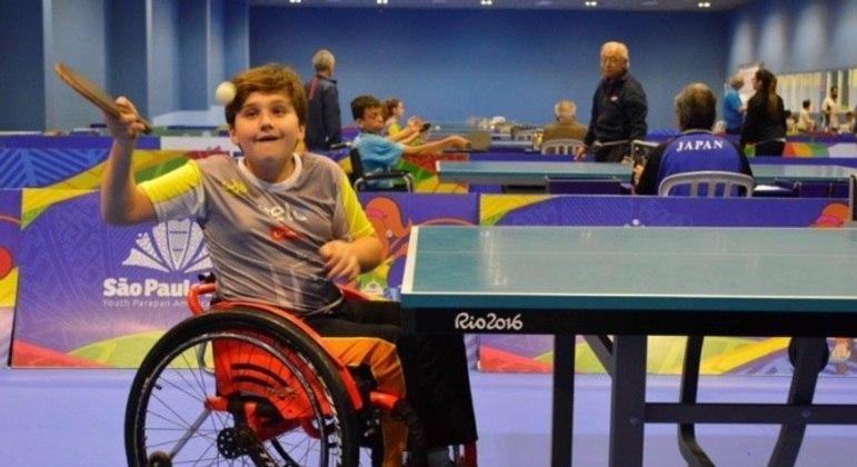 Foto de um garoto em uma cadeira de rodas jogando tênis de mesa
