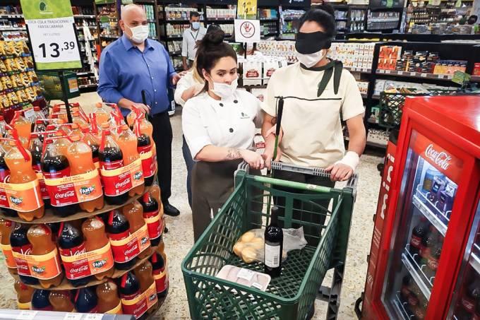 Foto de duas mulheres, ambas com uniforme do Pão de Açúcar, sendo que uma delas está com os olhos vendados e com uma bengala verde na mão esquerda enquanto empurra um carrinho com compras no interior do mercado