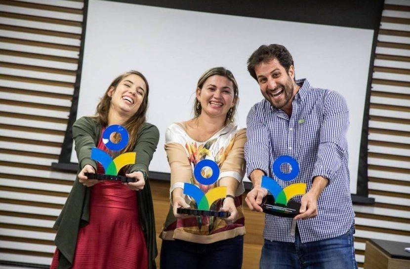Foto de duas mulheres e um homem, em pé, lado a lado, segurando nas mãos o troféu do Prêmio da Fundação Grupo Volkswagen