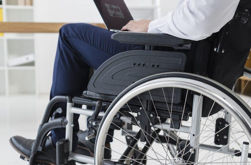Foto em close de um homem em uma cadeira de rodas com um laptop apoiado no seu colo. Ele veste uma calça e uma camisa social.