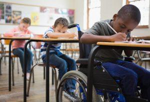 Foto de três crianças, sendo uma delas cadeirante, em uma sala de aula.